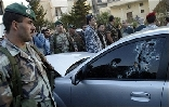 Lebanese security forces surround the bullet-riddled car of assasinated Lebanese Industry Minister Pierre Gemayel